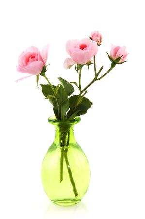 Pink roses in green glass vase isolated over white photo