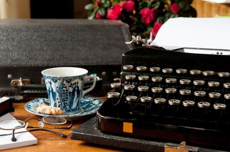 Old typewriter with glasses and cup of tea photo