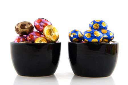 colorful easter eggs in black bowls isolated over white photo