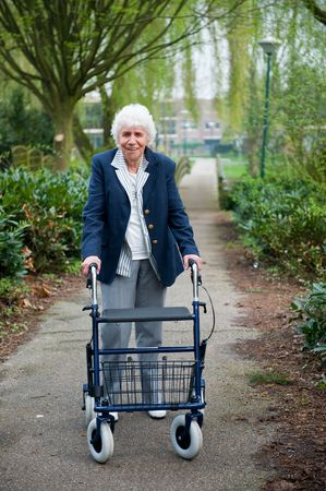 Very old lady with blue walker walking outdoor Stock Photo - 6503569