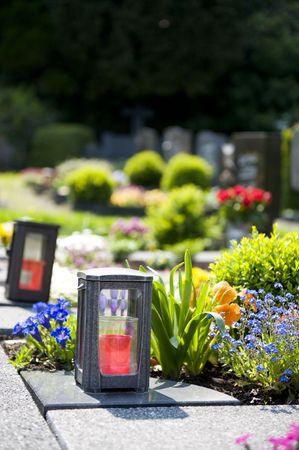 churchyard: cemetery in the sun with candles and flowers Stock Photo