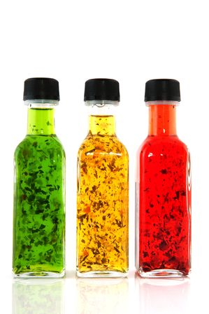 Colorful dressing with herbs in glass bottles photo