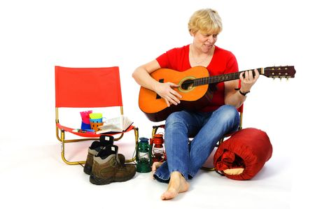 Senior woman is playing guitar at the campground photo