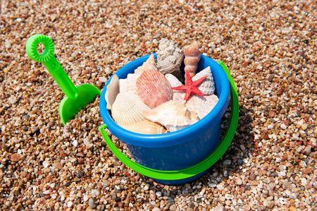 collect: Buscando obuses de la playa en un cubo de agua  Foto de archivo