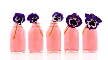 Row with purple Pansies in pink bottles Stock Photo - 6647474
