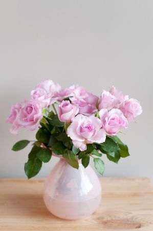 Pink roses in interior on gray wall photo