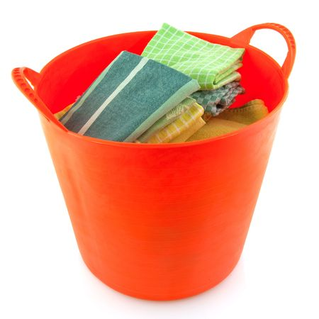 Folded laundry in a orange basket isolated over white photo