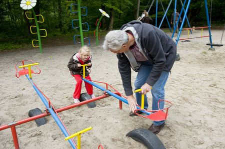 totter: Little girl is playing with her grandfather at the playground