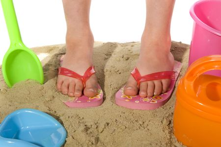 flip flops: child is playing in the sand with buckets and shovels Stock Photo