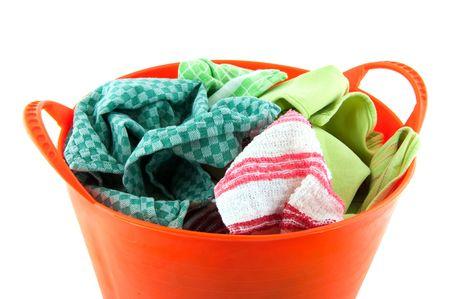 Orange plastic basket filled with laundry over white photo