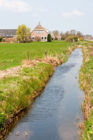 Dutch farmhouse in landscape with ditch and meadows Stock Photo