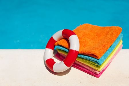 Folded towels and life buoy near the swimming pool photo