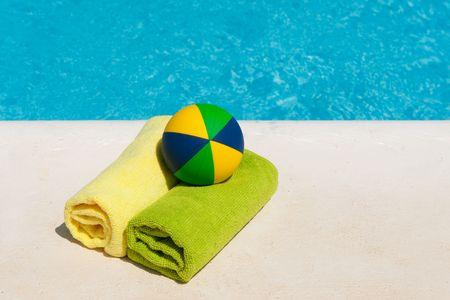 pool bola: Toallas enrolladas y juguetes cerca de la piscina