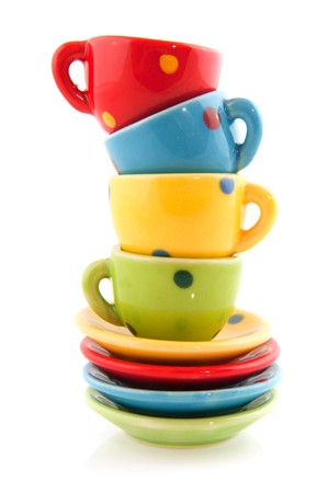 dishes: colorful stacked cups and saucers on white background