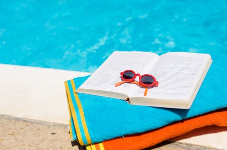 Leisure at the swimming pool with towels and a book