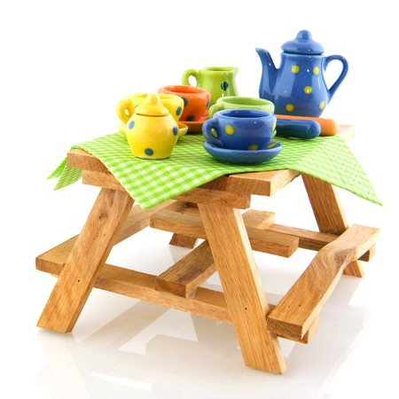 Picnic table with colorful crockery isolated white background Stock Photo