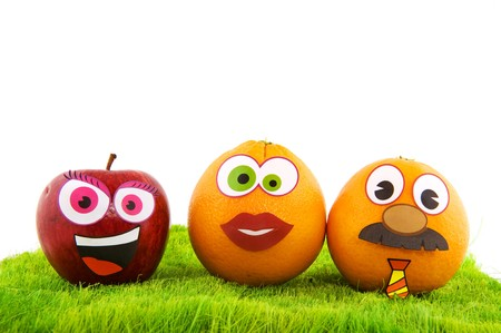 funny fruit: Funny healthy fruit family with faces in the grass Stock Photo