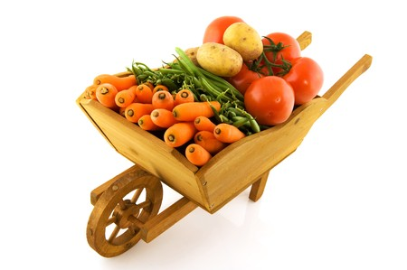barrow: wooden wheelbarrow full with fresh vegetables isolated over white