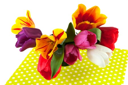 Colorful tulips in vase op spotted green background photo