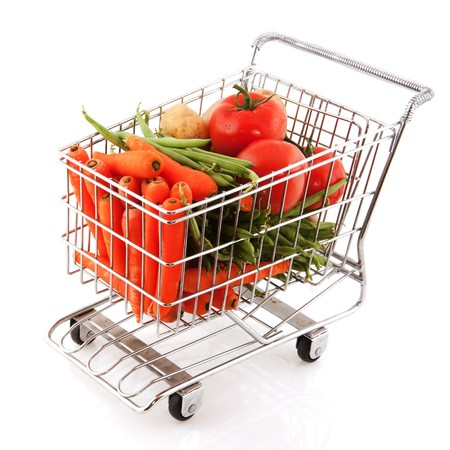 Shopping car full with fresh vegetables on white background