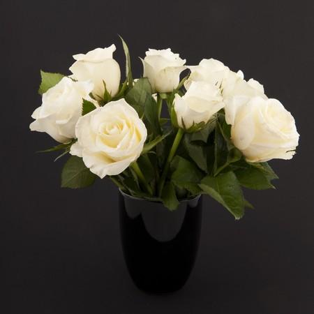 florero: Vaso de rosas blancas para un funeral aislados en negro
