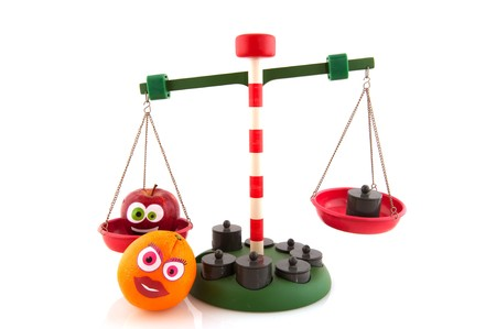 Balance with funny fruit for the right weight isolated over white photo