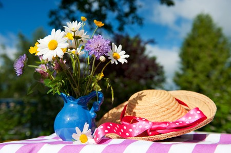Wild flowers as daisies and straw summer hat photo