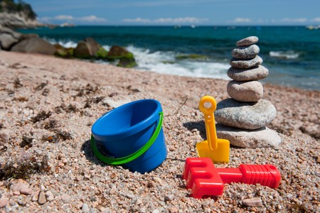 Landscape beach with stacked stones and plastic toys photo