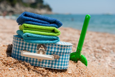 Travel with suitcase luggage and toys to the beach photo