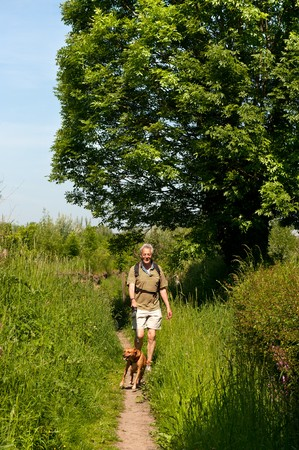 Elderly man is walking his dog in nature photo