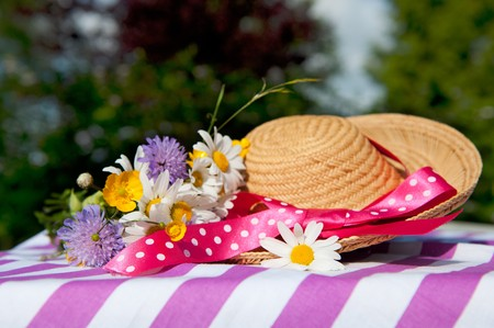 Wild flowers in the summer with straw hat photo