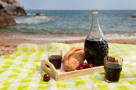 Wine bread and fruit at the picnic on the beach photo
