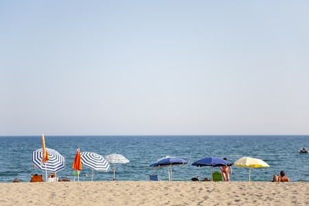 suntanning: vacation at the beach with people and parasols
