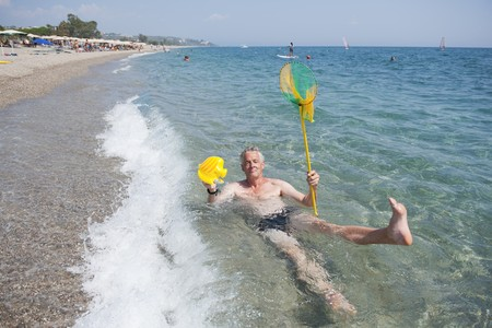 elderly man is playing in the sea with a fishing net photo