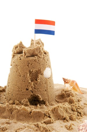 Sand castle with Dutch flag isolated over white photo