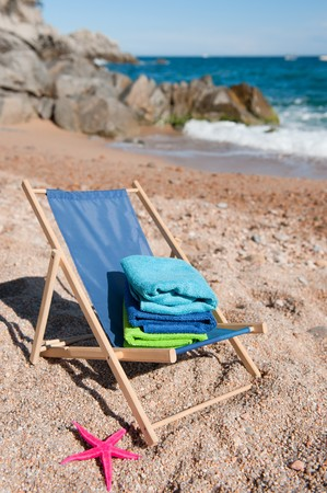 Beach chair with folded towels in vacation landscape photo