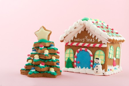 Cheerful gingerbread house and tree on a pink background photo