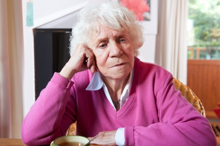 sad old woman: Very old woman in sitting at the table with cup of tea Stock Photo