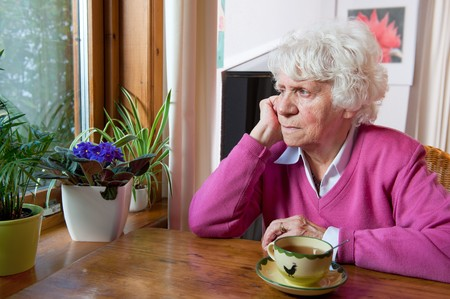 lonely person: Very old woman in sitting looking through the window Stock Photo