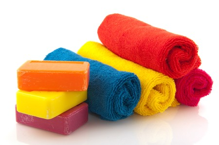 colorful rolled towels with bars soap isolated over white photo