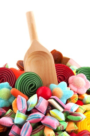 Many candy sweets with wooden spoon isolated over white