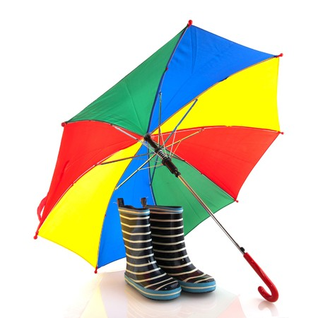 Rubber child boots and open umbrella isolated over white photo