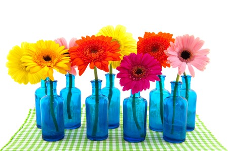 Row blue glass vases with colorful flowers isolated over white photo