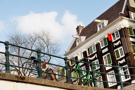 Bridge with bikes and old house in Amsterdam Stock Photo - 7828629