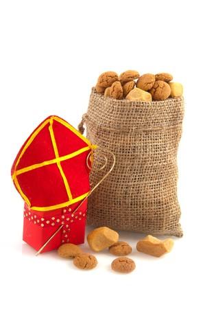 sinterklaas: Red Sinterklaas presents with pepernoten isolated over white