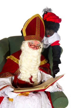 Sinterklaas and Black Piet reading in the big book Stock Photo - 7828869