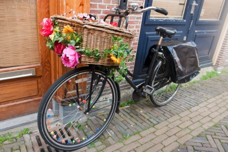 dutch: Dutch transport bike with basket and cheerful flowers Stock Photo