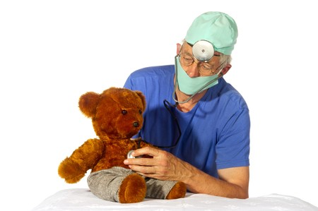 Doctor is having a medical treatment with stethoscope by toy bear photo