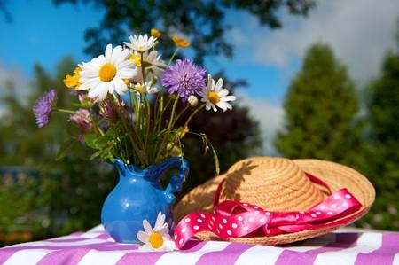 Wild flower bouquet in vase and summer hat the garden Stock Photo - 7934171