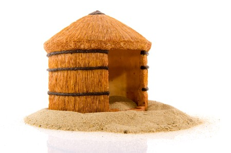 a house with a straw: African straw hut in the sand isolated over white